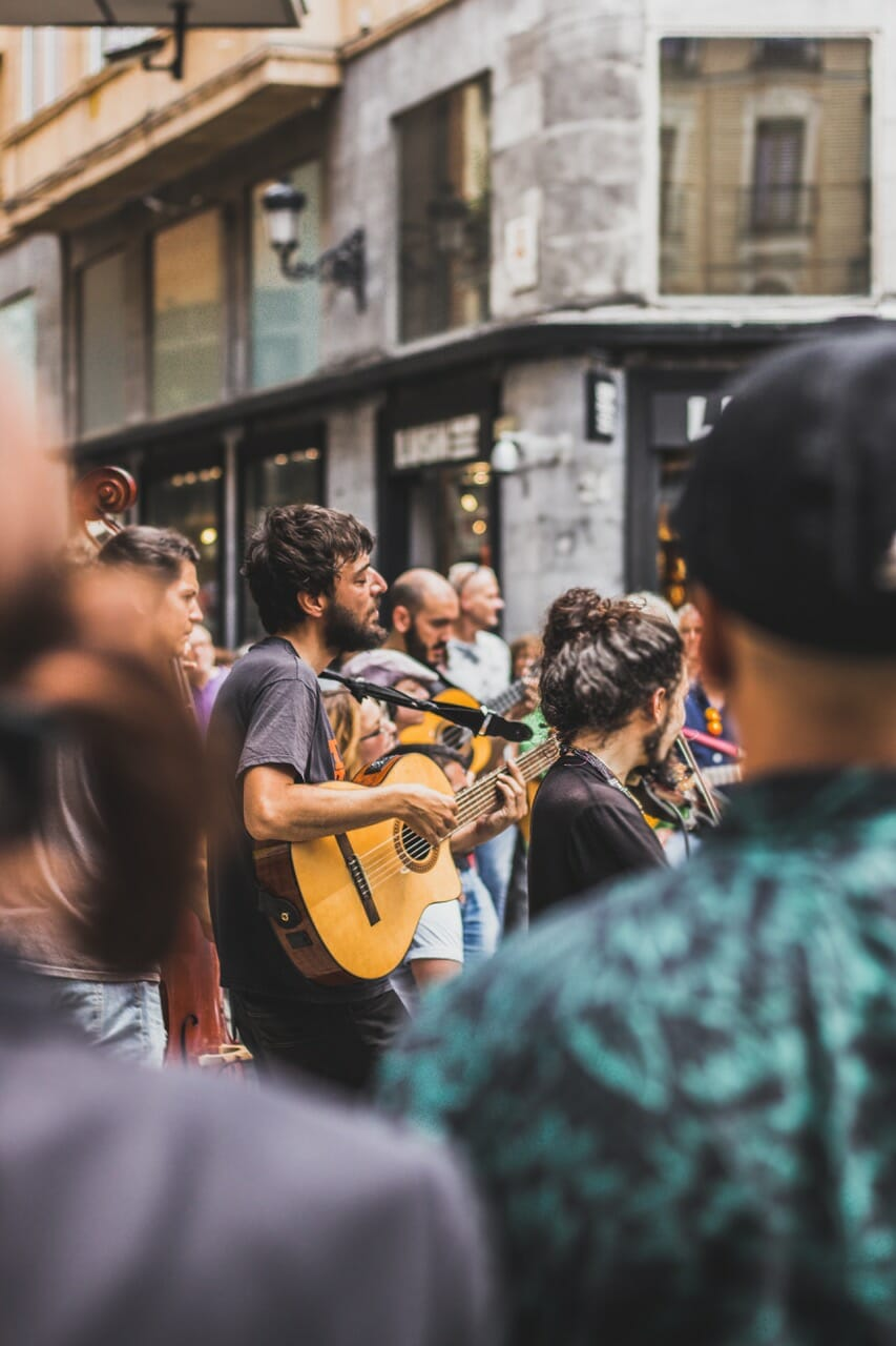 Group of People making music on guitars, violins, and other instruments in public